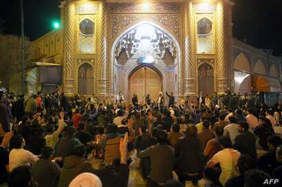 People gather outside the closed doors of the Fatima Masumeh shrine in Iran's holy city of Qom on March 16 2020. - Iran closed…