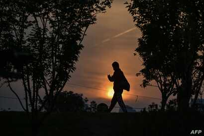 A man wearing a face mask walks at sunset in a park in Wuhan, in China's central Hubei province on April 19, 2020. - China's…