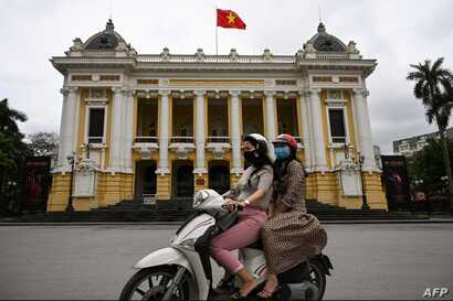 Women wearing face masks ride past the Opera House in Hanoi on April 23, 2020, as Vietnam eased its nationwide social isolation…