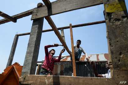 Villagers repair their house damaged by cyclone Amphan in Satkhira on May 22, 2020. - Bangladesh began a massive clean-up on…