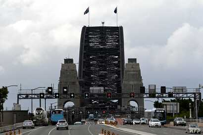 Motorists commute on the Harbour Bridge in Sydney on May 14, 2020. - New South Wales state will relax public gathering and…