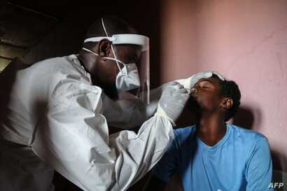 A staff member of the Ministry of Health take samples from a man during the first day of mass testing of the COVID-19…