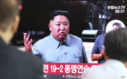 People watch a TV showing a file image of North Korean leader Kim Jong Un during a news program at the Seoul Railway Station in Seoul, South Korea, July 25, 2019. North Korea fired two unidentified missiles Thursday, South Korea's military said.