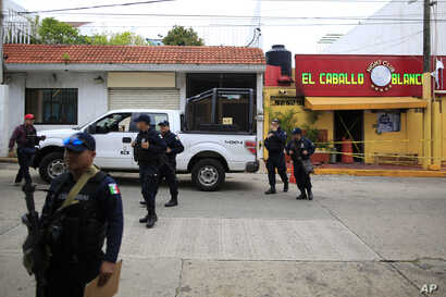 Police cordon off the White Horse nightclub (El Caballo Blanco in Spanish), the scene of a Tuesday night attack that killed more than two dozen staff and patrons, as they wait for federal investigators to arrive, in Coatzacoalcos, Veracruz state,…