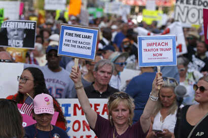 """Protesters hold signs during a """"We Stand Up"""" gathering, protesting a rally by President Donald Trump, Thursday, Aug. 1, 2019, in Cincinnati. (AP Photo/Gary Landers)"""