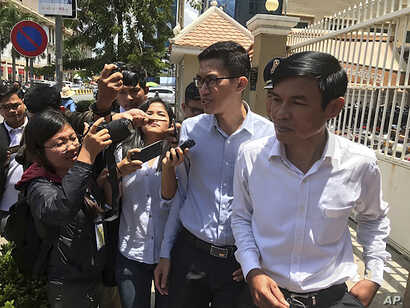 Journalist Yeang Sothearin, second from right, speaks to reporters as he and co-accused Uon Chhin step out of the municipal court in Phnom Penh, Cambodia, Friday, July 26, 2019. The espionage trial of the two Cambodian journalists who formerly…