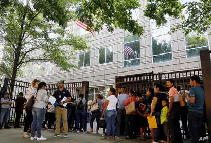 An Immigration and Customs Enforcement official assists people waiting to enter immigration court in Atlanta, June 12, 2019. U.S. authorities are fast-tracking families' cases to discourage many from making the journey to seek refuge in the United States.