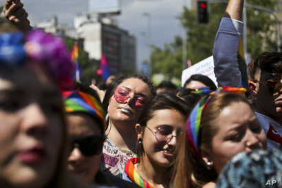 Participants take part in a gay pride parade in favor of equal marriage, the adoption and full equality of rights for lesbian, gay, bi, transgenders, intersex people and homo-parental families, in Santiago, Chile, Saturday, Nov. 17, 2018. (AP Photo…