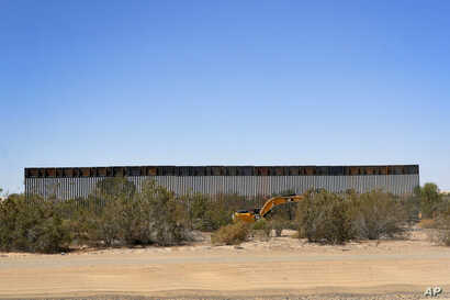 Government contractors erect a section of Pentagon-funded border wall along the Colorado River, Tuesday, Sept. 10, 2019 in Yuma, Ariz. The 30-foot high wall replaces a five-mile section of Normandy barrier and post-n-beam fencing along the the…