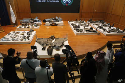 Journalists film what Saudi military spokesman Col. Turki al-Malki said was evidence of Iranian weaponry used in the attack targeted Saudi Aramco's facilities in Abqaiq and Khurais, during a press conference in Riyadh, Saudi Arabia, Wednesday, Sept…