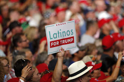 A supporter of President Donald Trump holds up a sign during campaign rally at the Santa Ana Star Center, Monday, Sept. 16, 2019, in Rio Rancho, N.M. (AP Photo/Andres Leighton)