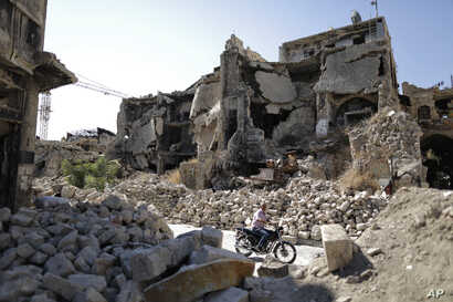 In this Saturday, July 27, 2019 photo, a man rides his motorcycle through the rubble of the old city of Aleppo, Syria. Rebels still frequently strike with shelling and mortars into Aleppo, killing civilians nearly three years after the government…