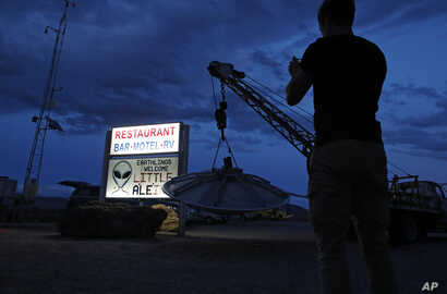 "A man takes a picture of a sign at the Little A'Le'Inn during an event inspired by the ""Storm Area 51"" internet hoax, Thursday, Sept. 19, 2019, in Rachel, Nev. Hundreds have arrived in the desert after a Facebook post inviting people to ""see them…"