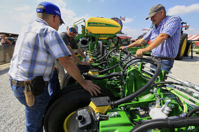 Visitors to the Husker Harvest Days farm show in Grand Island, Neb., look over John Deere equipment, Tuesday, Sept. 10, 2019. (AP Photo/Nati Harnik)