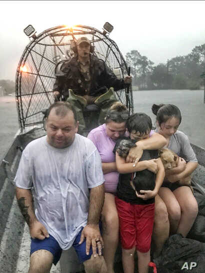 In this photo provided by the Texas Parks & Wildlife Department, a family is rescued via fan boat by a member of the department from the flood waters of Tropical Depression Imelda near Beaumont, Texas, Thursday, Sept. 19, 2019. (Texas Parks &…