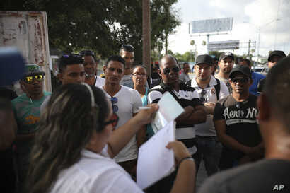 FILE - In this Aug. 2, 2019, file photo, migrants listen as a Mexican migration officer verifies their identity on a list Matamoros, Mexico, at the foot of the Puerta Mexico bridge that crosses into Brownsville, Texas. The U.S. has said at least 32…