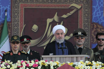 In this photo released by the official website of the office of the Iranian Presidency, President Hassan Rouhani speaks at a military parade marking 39th anniversary of outset of Iran-Iraq war, in front of the shrine of the late revolutionary…