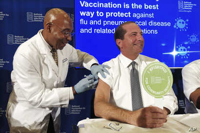 B.K. Morris, a nurse with MedStar Visiting Nurses Association, gives a flu shot to Secretary of Health and Human Services Alex…