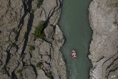 In this June 25, 2019 photo, people raft on the Vjosa River near Permet, Albania. Some tout hydropower as a reliable, cheap and…