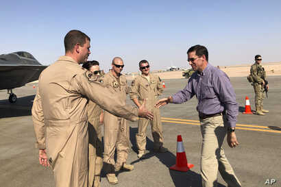 Defense Secretary Mark Esper talks with U.S. troops in front of an F-22 fighter jet deployed to Prince  Sultan Air Base in…