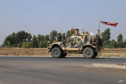 A U.S. military vehicle, part of a convoy, arrives near Dahuk, Iraqi, Monday, Oct. 21, 2019. Defense Secretary Mark Esper said…