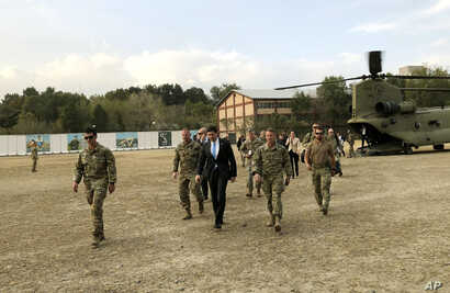 U.S. Defense Secretary Mark Esper, center, walks Gen. Scott Miller, right, chief of the U.S.-led coalition in Afghanistan, at…