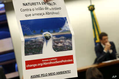 """An environmentalist holds a sign that reads in Portuguese """"Nature at Risk: Against the Abrolhos Threatening Oil Auction"""" during…"""