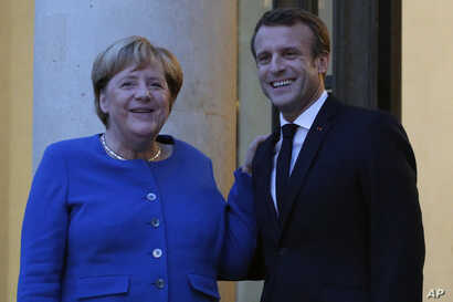 French president Emmanuel Macron welcomes German Chancellor Angela Merkel prior to their meeting at the Elyse Palace in Paris,…