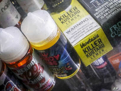 FILE- In this Sept. 16, 2019 file photo Flavored vaping solutions are shown in a window display at a vape and smoke shop in New…