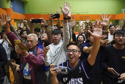 Supporters of pro-democracy candidate Angus Wong celebrate after he won in district council elections in Hong Kong, early…
