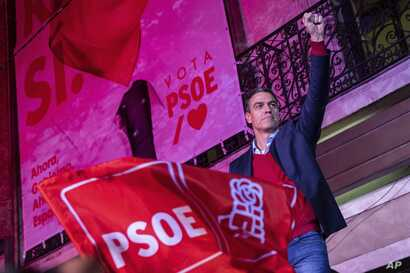 Spain's Prime Minister and Socialist Party leader Pedro Sanchez gestures to supporters outside the party headquarters following…