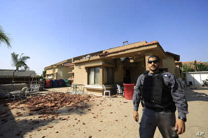 A policeman stands in front of a house hit by a rocket fired from Gaza Strip in Netivot, Israel, after it was hit by a rocket…