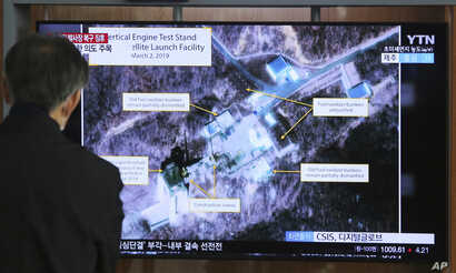FILE - In this March 6, 2019 file photo, a man watches a TV screen showing an image of the Sohae Satellite Launching Station in…
