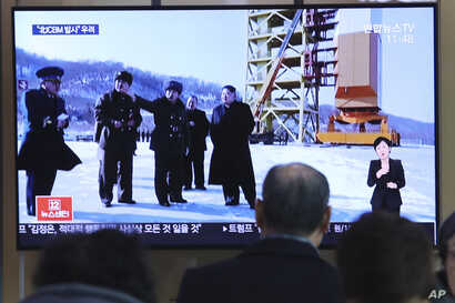 A man watches a TV screen showing a file image of the North Korean leader Kim Jong Un at his county long-range rocket launch…