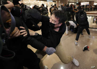 Plain clothed police officers arrest protesters in a mall during Christmas Eve in Hong Kong, Tuesday, Dec. 24, 2019. Thousands…