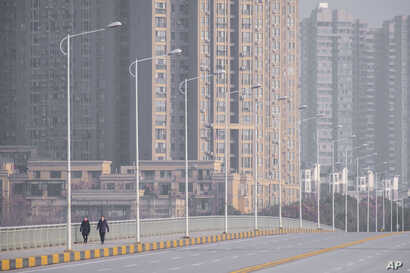 People wearing face masks walk down a deserted street in Wuhan in central China's Hubei Province, Tuesday, Jan. 28, 2020. China…