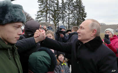 President Vladimir Putin, right, shakes hands with a man after attending a wreath laying commemoration ceremony for the 77th…