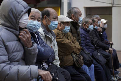 Elderly men sit at a park wearing face masks in Hong Kong, Thursday, Jan. 30, 2020. Hong Kong cut off rail service to mainland…