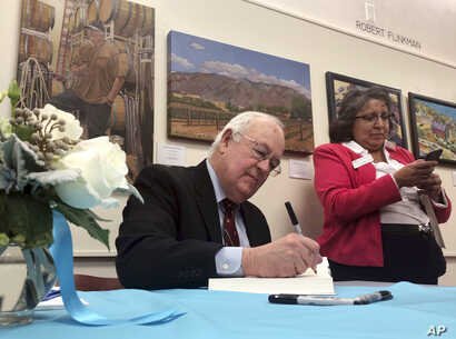 """Former independent counsel Kenneth Starr signs a copy of his recent book """"Contempt: A Memoir of the Clinton Investigation"""" at…"""