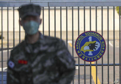 In this Feb. 21, 2020, photo, a South Korean marine wearing a mask stands in front of the Navy Base after a soldier of the unit…