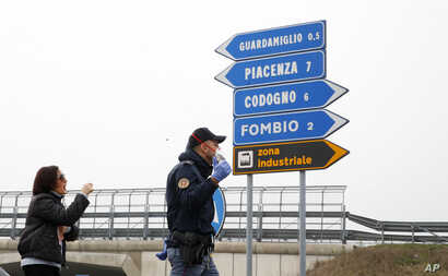 A police officer discusses with a woman as he checks transit to and from the cordoned area in Guardamiglio, Italy, Tuesday, Feb…
