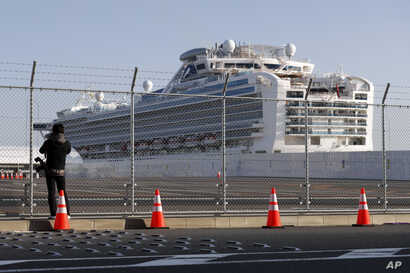 A photographer takes photos near the quarantined Diamond Princess cruise ship anchored at a port in Yokohama, near Tokyo,…