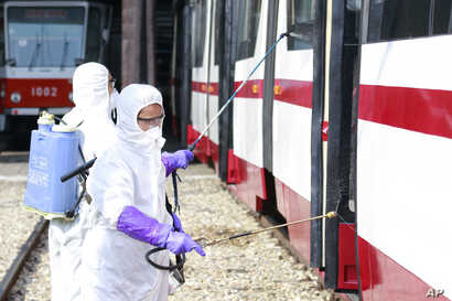 Members from an emergency anti-epidemic headquarters in Mangyongdae District, disinfect a tramcar of Songsan Tram Station to…