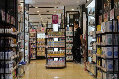 In this Oct. 30, 2019, photo, a salesman waits for customers at a cosmetic shop in a shopping district in Hong Kong. Business…