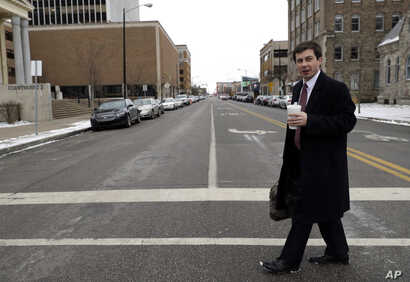 Mayor Pete Buttigieg talks with an AP reporter as he walks in downtown South Bend, Ind., Thursday, Jan. 10, 2019.  Few people…