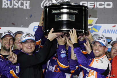 Denny Hamlin, right, celebrates as he and crew members hoist the championship trophy after winning the NASCAR Daytona 500 auto…