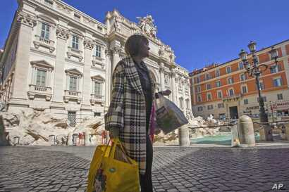 A woman walks by the Trevi fountain in Rome, Thursday, March 12, 2020. Italians woke up to yet further virus-containment…