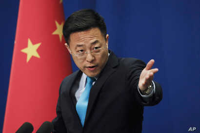 Chinese Foreign Ministry new spokesman Zhao Lijian gestures as he speaks during a daily briefing at the Ministry of Foreign…