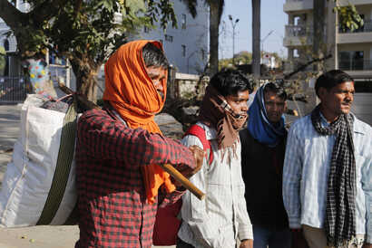 Daily wage laborers leave for their respective villages as the city comes under lockdown in Prayagraj, India , Thursday, March…