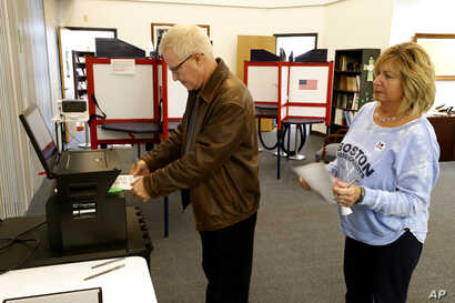 Greg Froehlinch and his wife Deb of Steubenville, Pa., take advantage of early voting, Sunday, March 15, 2020, in Steubenville,…